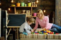 Familiespel met aannemer thuis Mamma en kindspel met details van aannemer, plastic bakstenen moeder en zoon royalty-vrije stock fotografie