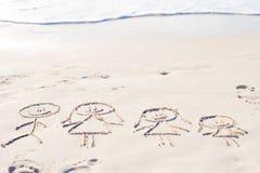 Familiesymbool op strand wit zand dat wordt getrokken Stock Afbeelding