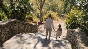 Familietijd De moeder en de dochter lopen beneden bij de landweg op de heuvel van tropisch eiland Toneel gezichtspunt stock videobeelden