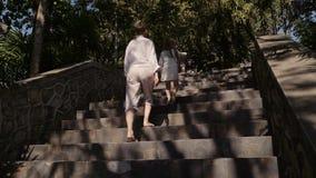 Familietijd De moeder en de dochter lopen boven bij de landweg op de heuvel van tropisch eiland Toneel gezichtspunt stock videobeelden