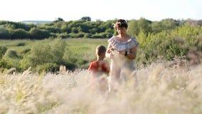 Familievakantie in aard - de moeder en de zoon wandelen door het de zomergebied stock video