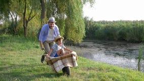 Familievakantie in platteland, vrolijke vaderdwaas rond met zijn zoon in kruiwagen dichtbij kleine rivier stock videobeelden