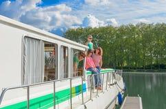 Familievakantie, reis op aakboot in kanaal, gelukkige ouders met jonge geitjes die pret op riviercruise hebben in woonboot Stock Foto's