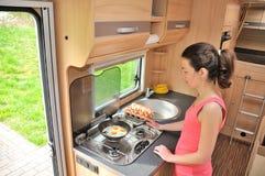 Familievakantie, rv-vakantiereis, reis en het kamperen, vrouw het koken in kampeerauto, motorhome binnenland stock foto