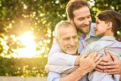 familievergadering Een mens en een jongen kwamen hun grootvader zien die in een park op een rolstoel zit royalty-vrije stock foto's