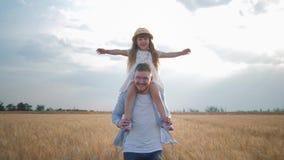 Familievermaak op gebied, gelukkige jonge papa met weinig jong geitjemeisje in strohoed op zijn schouders die haar handen uitspre stock video
