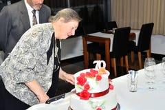 Familieviering en snijdende cakes voor de 70ste verjaardag royalty-vrije stock afbeelding