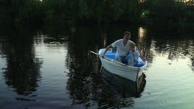 Familievlotters op een boot op het meer stock videobeelden