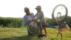Familievrije tijd, jong geitje en vader die fiets herstellen bij landelijk op achtergrond van aard in backlight stock video