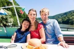 Familiezitting gelukkig op boot op riviercruise in de zomer royalty-vrije stock afbeelding