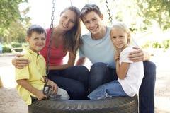 Familiezitting op Bandschommeling in Speelplaats Stock Foto's
