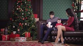 Familiezitting op een leerbank dichtbij de Kerstboom waaronder vele giften in een pakket zijn Vader het spelen met stock footage