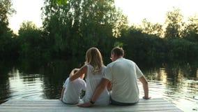 Familiezitting op meer door groene aard wordt omringd die stock videobeelden