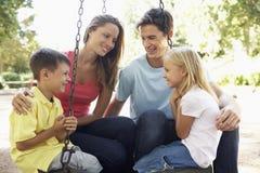 Familiezitting op Schommeling in Speelplaats Royalty-vrije Stock Afbeeldingen