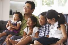 Familiezitting op Sofa At Home Watching-TV samen Stock Afbeelding