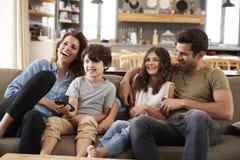 Familiezitting op Sofa In Open Plan Lounge-het Letten op Televisie royalty-vrije stock fotografie