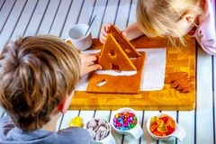 Familiy building a sweet ginger bread house royalty free stock photos