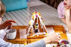 Familiy building a sweet ginger bread house stock photos