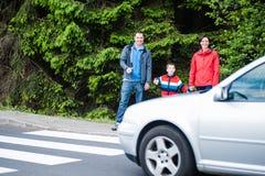 Familiy, das durch den Crosswalk wartet Stockbild