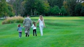 Familiy feliz con el soldado del padre que camina adelante, opinión de la parte posterior metrajes