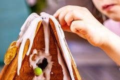 Familiy que constrói uma casa doce do pão do gengibre fotografia de stock royalty free