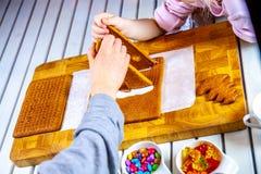 Familiy que construye una casa dulce del pan del jengibre fotografía de archivo
