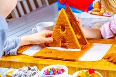 Familiy que construye una casa dulce del pan del jengibre imagen de archivo