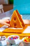 Familiy que construye una casa dulce del pan del jengibre imagenes de archivo