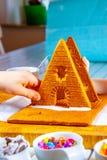 Familiy que construye una casa dulce del pan del jengibre foto de archivo