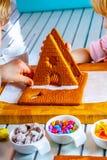 Familiy que construye una casa dulce del pan del jengibre fotografía de archivo libre de regalías
