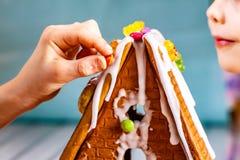 Familiy que construye una casa dulce del pan del jengibre fotos de archivo libres de regalías