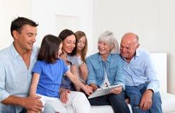 Familj av användande tablet 6 hemma Royaltyfri Foto