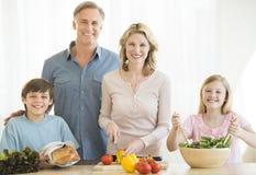 Familj av förberedande mat fyra tillsammans på räknaren arkivfoto