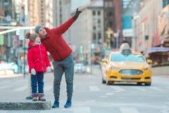 Familj av fadern och den lilla ungen på Times Square under deras semester i New York City arkivbild