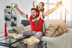Familj av fans som hemma håller ögonen på en fotbollsmatch på TV Royaltyfri Foto