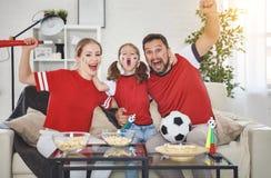 Familj av fans som hemma håller ögonen på en fotbollsmatch på TV royaltyfria foton