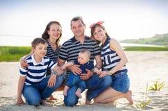 Familj av fem som har gyckel på stranden Arkivfoton