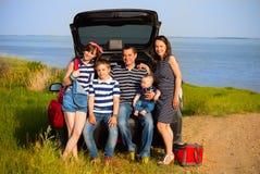 Familj av fem som har gyckel på stranden som går på sommarsemester Royaltyfria Bilder