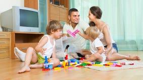 Familj av fyra hemma med leksaker Arkivbilder