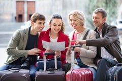 Familj av fyra med bagage som kontrollerar riktning i översikt royaltyfri bild