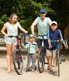 Familj av fyra med cyklar och sparkcykeln i semester Arkivbilder