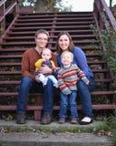 Familj av fyra på trappa arkivfoto