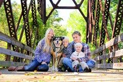 Familj av fyra personer- och hundsammanträde på bron i höst Royaltyfri Foto