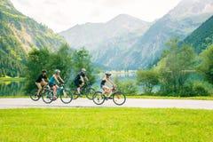 Familj av fyra som cyklar Arkivfoto