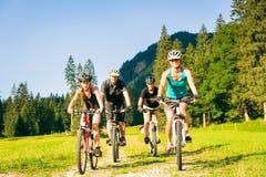 Familj av fyra som cyklar fotografering för bildbyråer