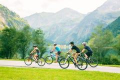 Familj av fyra som cyklar Arkivbild