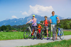 Familj av fyra som cyklar royaltyfri bild