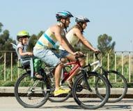Familj av fyra som cyklar på gatan Arkivfoton