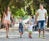 Familj av fyra som går med barn på solig dag Royaltyfri Foto