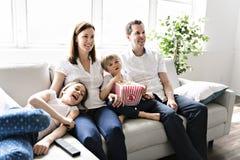 Familj av fyra som har gyckel på soffan hemma som håller ögonen på film med popcorn arkivfoto